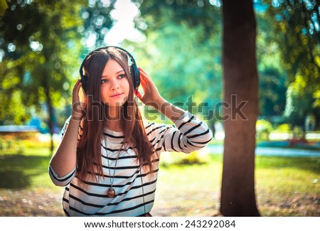 Young girl listening to music in headphones in park. Happy young teenager student of Caucasian ethnicity  - stock photo