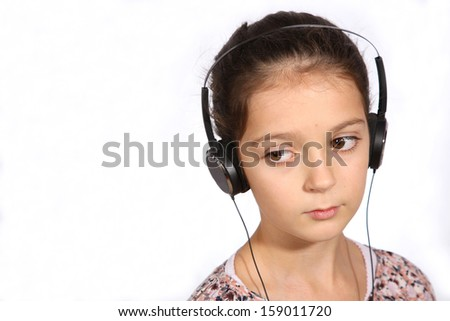 Young girl listening to music on earphones on a white background