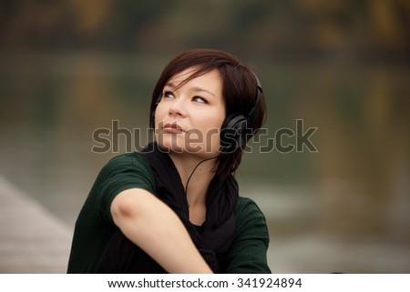 Young girl listening to the music in the autumn park - stock photo