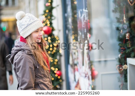 Young girl looking at Parisian shop-windows decorated for Christmas - stock photo