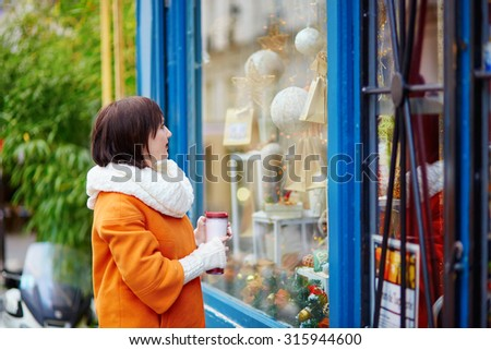 Young girl looking at Parisian shop-windows decorated for Christmas. holding take away hot beverage - stock photo