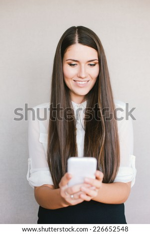 young girl looking at phone and smiling - stock photo