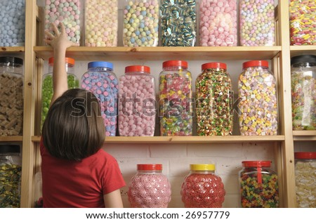 young girl looking at rows of sweets in shop