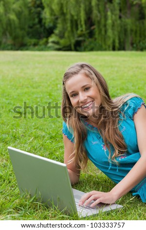 Young girl looking at the camera while typing on her laptop and showing a great smile