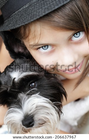 Young girl looking directly into the camera, wearing a fashionable black hat and snuggling her puppy. Extreme shallow depth of field with selective focus on eyes.