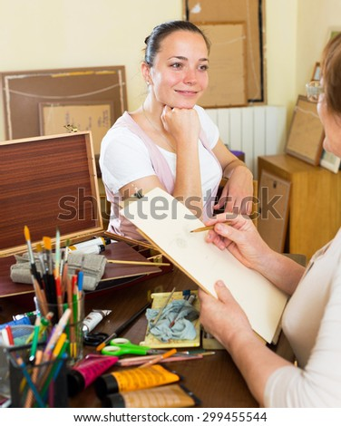Young girl looking for Artist painting his portrait at workshop - stock photo