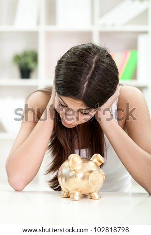 young girl looking in her piggybank and checking savings - stock photo