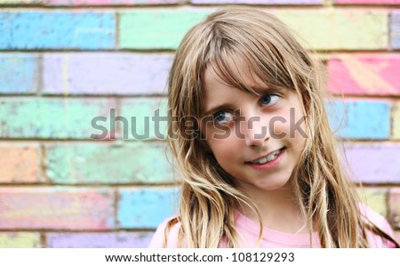 Young girl looking left with colorful brick work as background