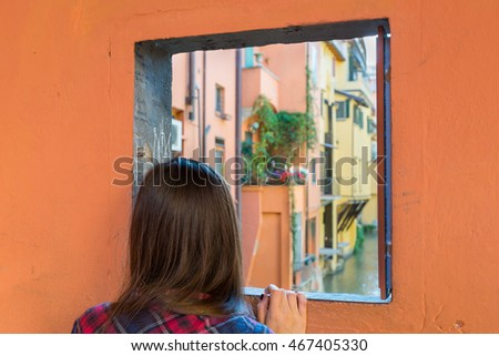 Young girl looking outside a window located at Little Venice, in Bologna, Italy