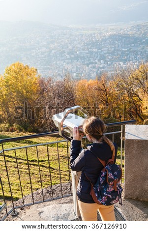 Young girl looking through a coin operated binoculars at Monte Bre, Lugano, Switzerland - stock photo