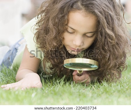 Young girl looking through magnifying glass at grass - stock photo