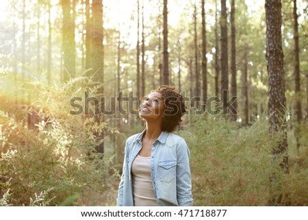 Young girl looking up into the pine trees in a plantation in the late afternoon sun while wearing casual clothing