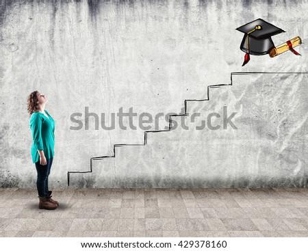 Young girl looking up towards a diploma, aspiration - stock photo