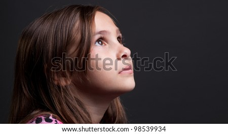 Young girl looking up with plenty of room for copy - stock photo