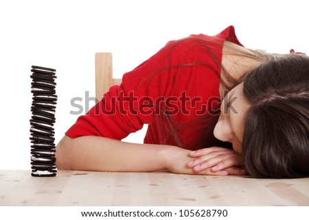 Young girl looks at cookies. Head and hands are based on the table. Isolated on the white background.
