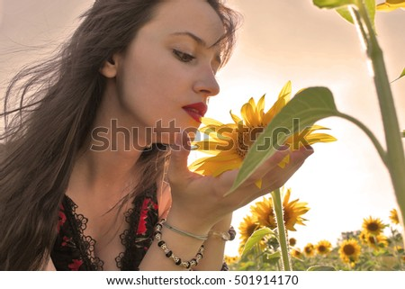 Young girl looks at sunflower - focus is on the flower