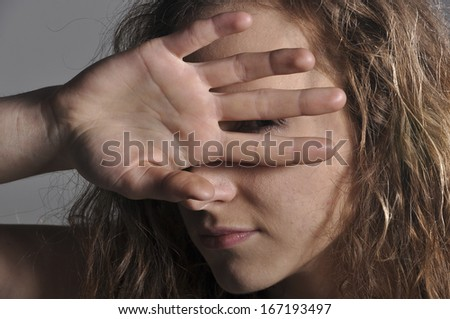 young girl looks through fingers
