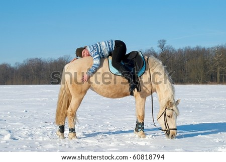 Young girl lying back to front on a horsback - stock photo