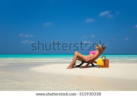 Young girl lying on a beach lounger with glasses in hand on the tropical island