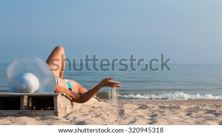 Young girl lying on a beach lounger with sand in the hand on the seafront - stock photo