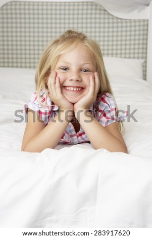 Young Girl Lying On Bed Smiling - stock photo