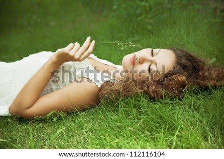 Young girl lying on green grass - stock photo