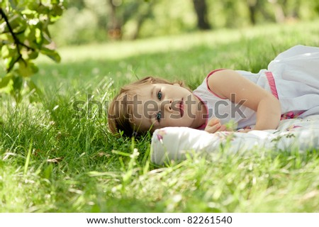 Young girl lying on green grass in the park