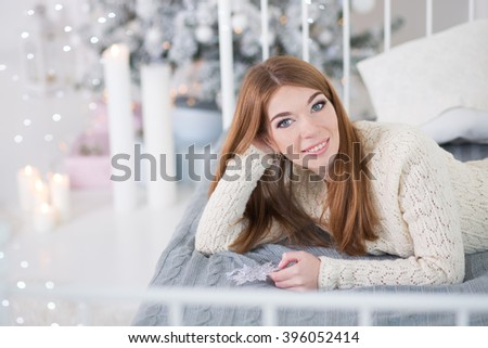 Young girl lying on the bed and smiling.New Year relaxing time.Happy Holidays.Cozy day with candles.Around candls and lights.Red haired woman on a bed. - stock photo