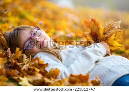 Young girl lying on the colored maple leaves in hands holding a bouquet from the same leaves.