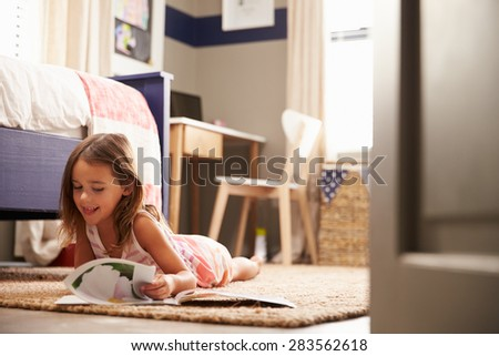 Young girl lying on the floor reading - stock photo
