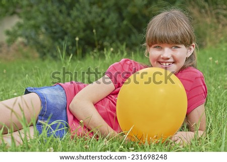 Young girl lying on the grass with balloon - stock photo