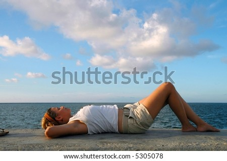 Young girl lying relaxing by the ocean
