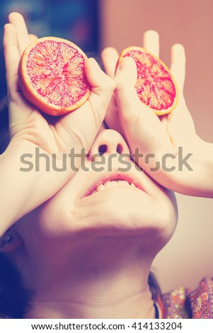 Young girl make face with two halves of grapefruit