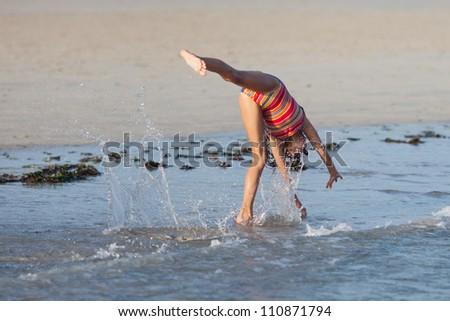 young girl makes a cartwheel at the beach - stock photo