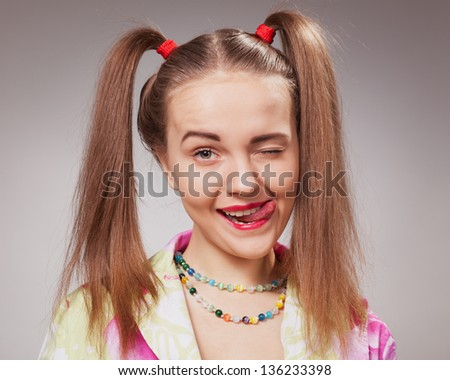 young girl makes funny face in closeup over grey background