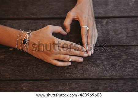 Young girl making a sing love with her hands on a rustic wooden table. Boho style, wearing rings