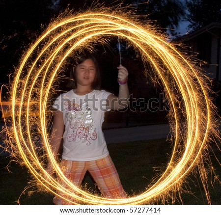 Young girl making circles with a sparkler - stock photo