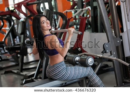 Young girl making exercise on the fit ball with dumb-bells. Young girl in the gym working out on sports trainer. Smiling sporty girl wearing sportswear. Fitness training. Workout. - stock photo