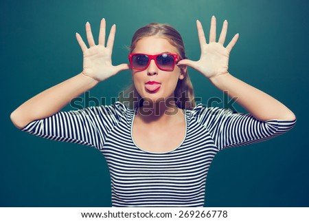 Young girl making face in front of blackboard, intentionally toned - stock photo