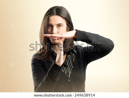 Young girl making time out gesture over ocher background  - stock photo