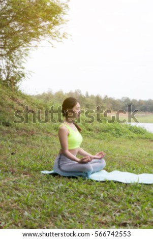 young girl meditates while practicing yoga. freedom, calmness and relax concept, woman happiness (blur image)