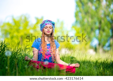 Young girl meditating in the park - stock photo