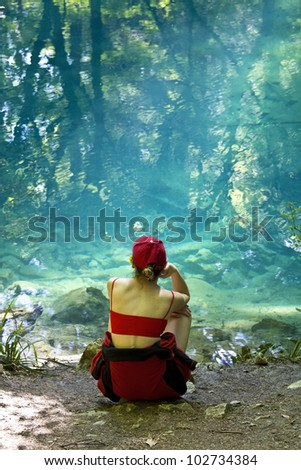 Young girl meditating near a blue lake with trees reflected in water