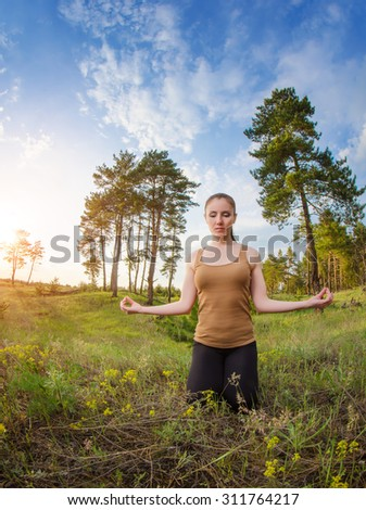 Young girl meditating outdoors on a background of blue sky and green field