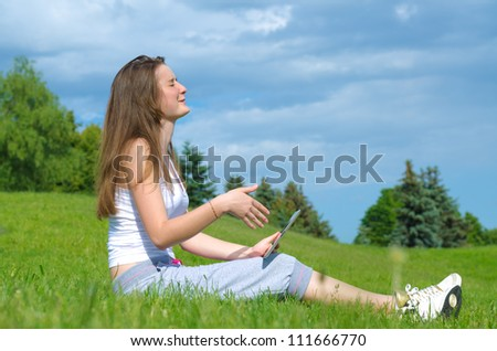 Young girl memorising something on her tablet with her eyes closed as she studies for her classes in the park