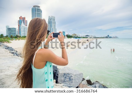 young girl model taking pictures of the ocean - stock photo