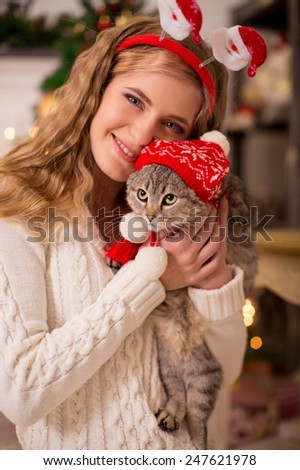 Young girl near a new-year tree with a cat in the cap of Santa