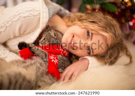 Young girl near a new-year tree with a cat in the cap of Santa - stock photo