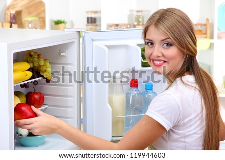 Young girl near refrigerator in kitchen