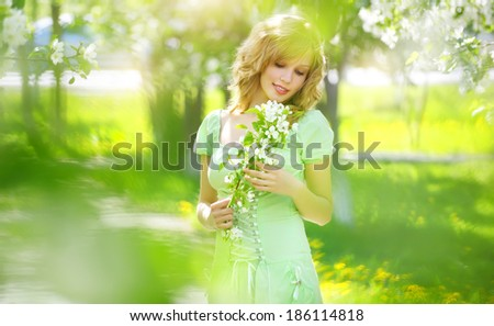 Young girl near the apple tree. light background - stock photo